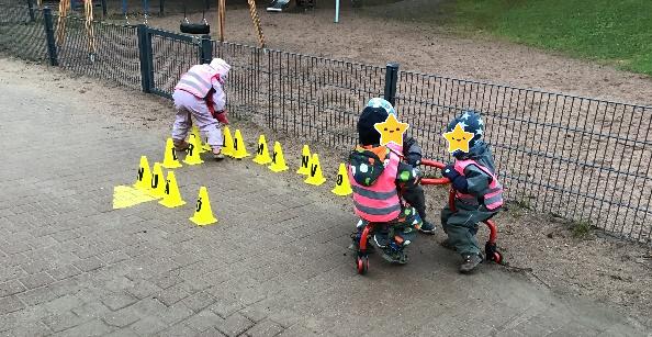 Lapset leikkivät karusellipyörällä. Yksi lapsista järjestelee aakkoskartioita.